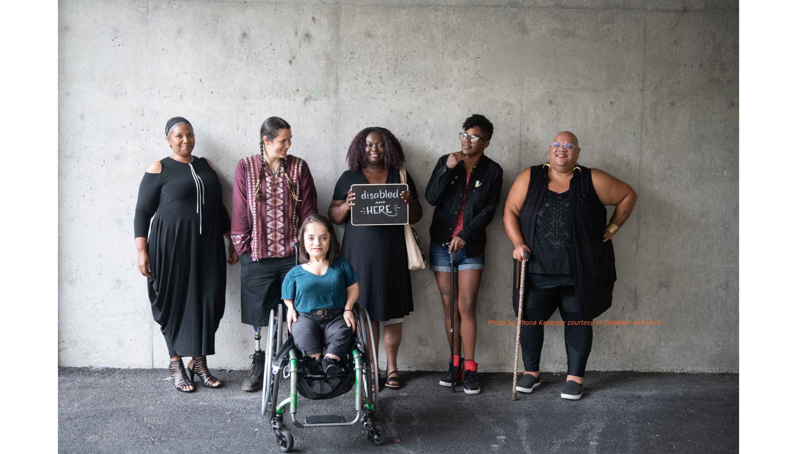"Five people smile and stand leaning against a wall. Two of them use canes. At center, a Black woman with long curly hair wears a black dress, smiles, and holds a sign that reads ""disabled and HERE"". Another woman in front, also smiling, sits in a wheelchair."
